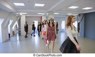Young models walk in one line to train before going on stage.