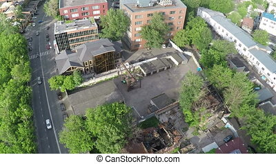 Aerial shot of street with car traffic and ruined house -...