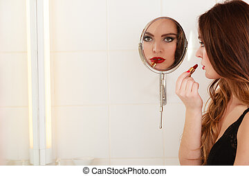 Young girl making makeup in bathroom. Woman take care about...