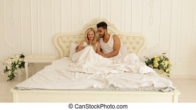 Couple lying bed using tablet computer, mix race man woman smile morning bedroom