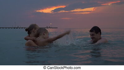 At sunset mother with son swim in sea of city Perea, Greece