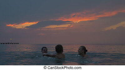 At sunset mother, father with their son swimming in sea of city Perea, Greece