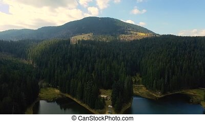 Aerial drone footage of lake and mountains against sky. Fast...