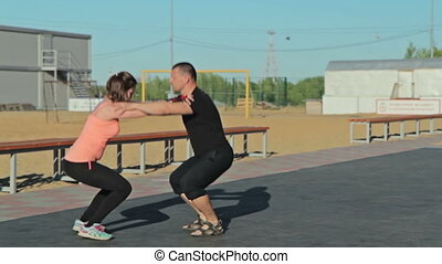 Man and girl squatting together, crossfit workout