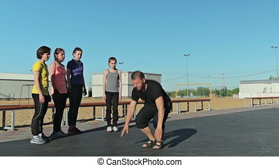 A man show how to do burpee, pushups and another exercise,...