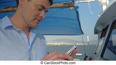 Man is typing on his smartphone while he sails on the boat...