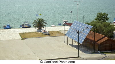 Solar panels are fixed next to the house, in the background is a calm sea