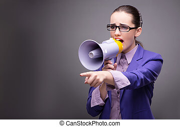 Young businesswoman yelling through loudspeaker