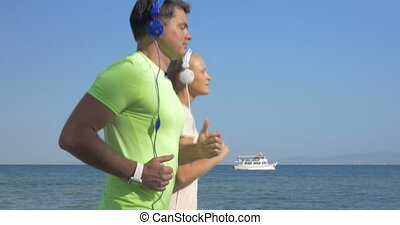 Shot of young woman and man in headset are jogging on sea skyline background Piraeus, Greece