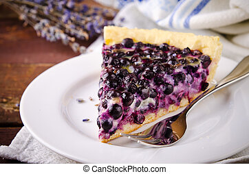Bilberry, blueberry tart with lavender on white plate,...