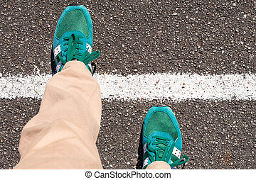 Concept of achievement. - A pair of feet taking a step on an...