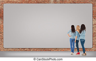three women looking at a big blank billboard - back view of...