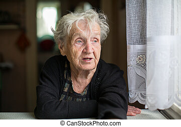 Elderly woman portrait at the kitchen table.