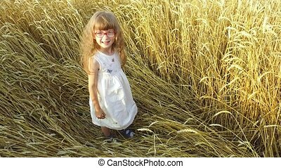 Little girl lies on a haystack Straw in a wheat field. Wheat...