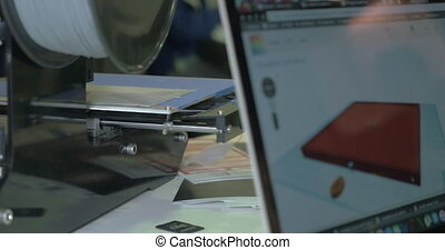 Working 3D printer and laptop with model on screen - Laptop...