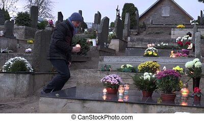 Mourning man kneel on grave at cemetery and pray with burn...