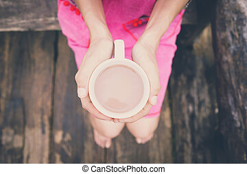 Woman holding a cup of coffee in the morning