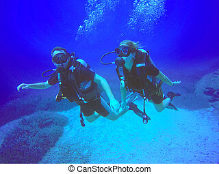 Scuba divers - A scuba diver couple applying the buddy...