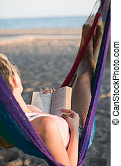 relaxed woman laying in hammock bed on beach and enjoy...