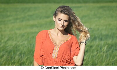 Close-up portrait of a beautiful blonde young romantic woman in a red shirt touching her hair at the green field