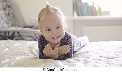 Smiling little girl lying on the bed.