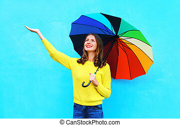 Happy pretty smiling young woman with colorful umbrella in...