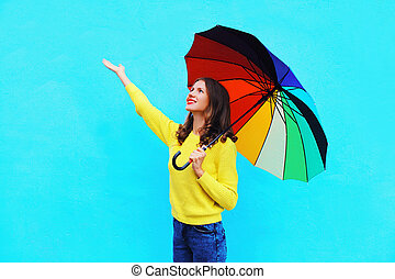 Happy smiling young woman holding colorful umbrella in...