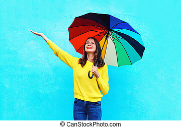 Happy smiling young woman with colorful umbrella in autumn...