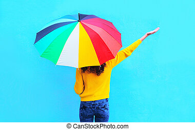 Happy young woman with colorful umbrella raised hands up...