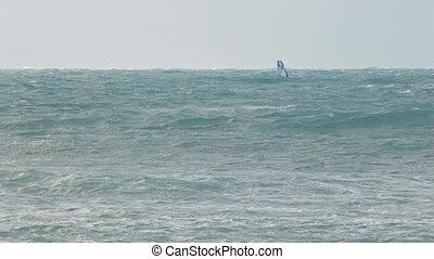 Winter windsurfing in a storm - man surfing in strong winds...