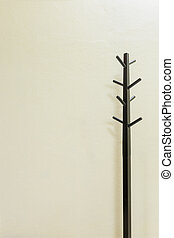 Black wooden coat rack on wall background, copy space.