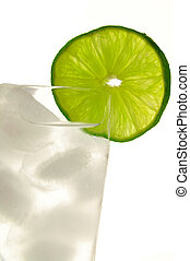 Tall glass of ice water with lime slice
