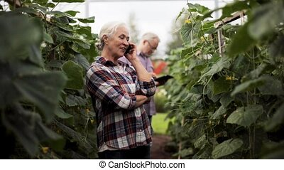 old woman calling on smartphone in farm greenhouse -...