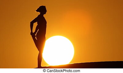 woman stretching in sunset with huge sun.mov