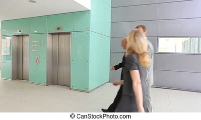 businessteam of three using elevator TWO TAKES - three...