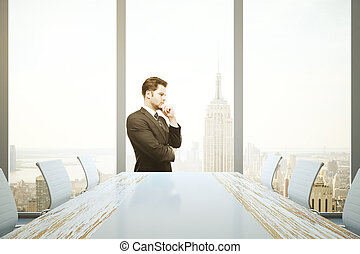 Man in conference room - Thoughtful businessman standing in...