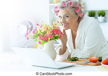 Senior woman in  hair rollers at kitchen
