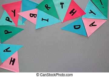 Party colorful flags on grey table with worlds HAPPY...
