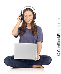 Leisure activity - Woman with headphones and laptop looking...