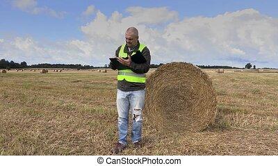 Farmer writing on the field near straw bales