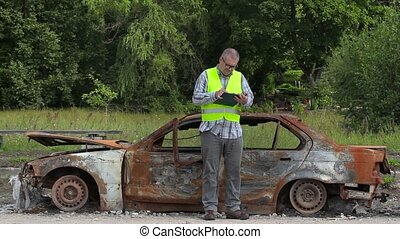 Inspector writing near the car wreck on road