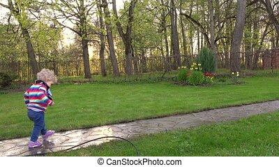 Child girl walk on wet path after rain in summer garden....