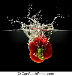 Red bell pepper falling in water, black background - Red...