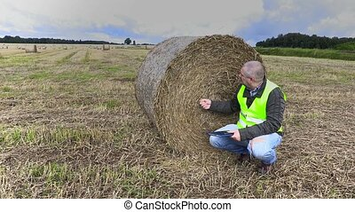 Farmer on field checking the straw bale