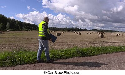 Farmer talking on the smartphone and walking away on the...