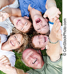Multi-generation family lying in circle and laughing at...