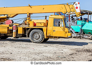 Old yellow heavy truck mobile crane at building site - Rusty...