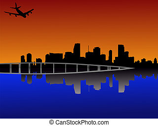 Miami at sunset with plane - Miami Florida skyline reflected...