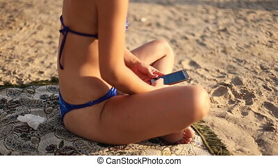 beautiful girl with a phone on the beach