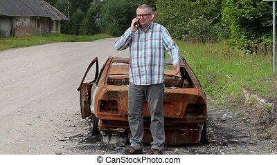 Stressful man talking on smart phone and kick car wreck